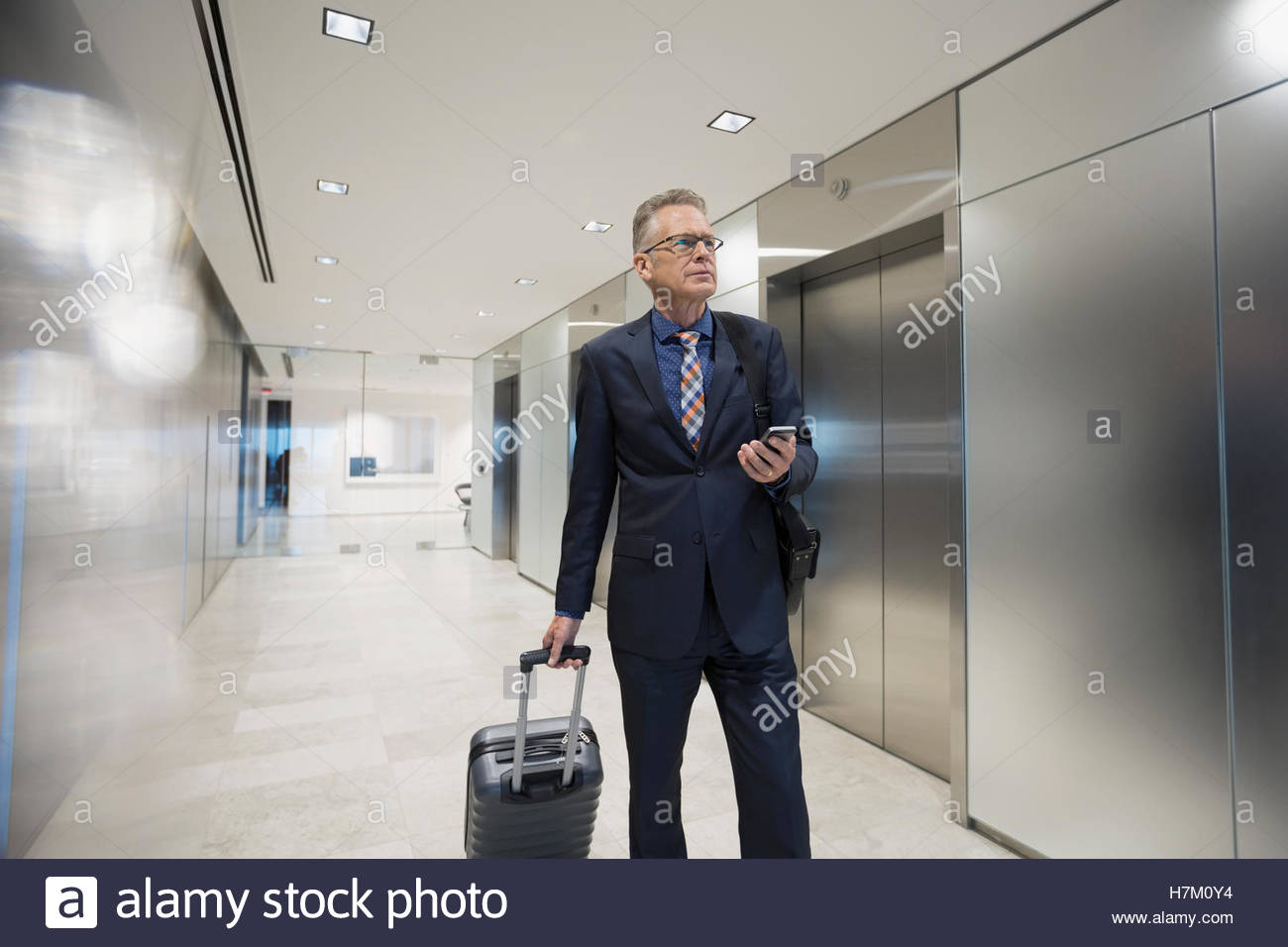 Businessman with cell phone pulling luggage past elevators in airport corridor - Stock Image