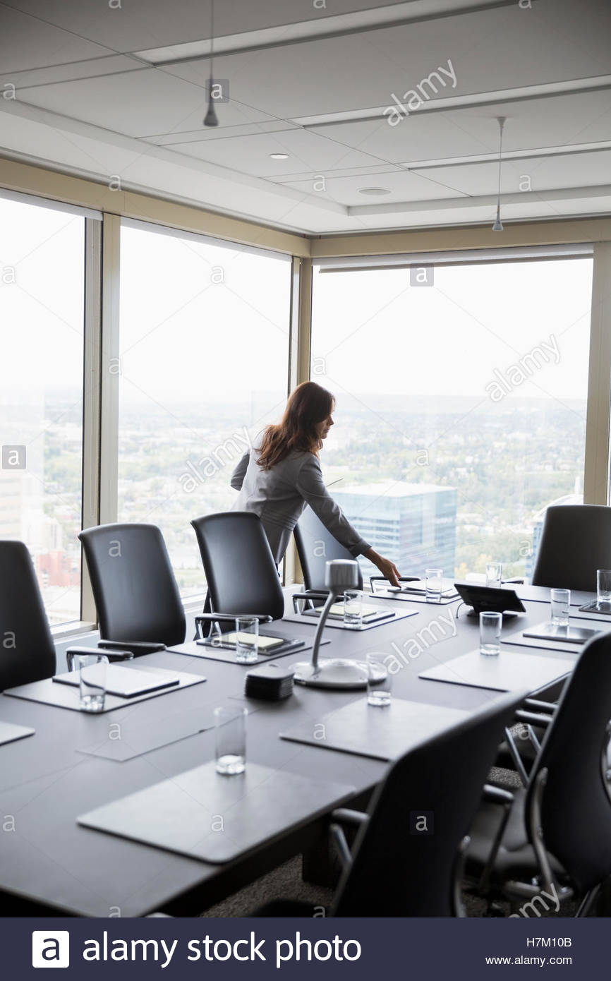 Businesswoman preparing for meeting placing paperwork on conference room table - Stock Image