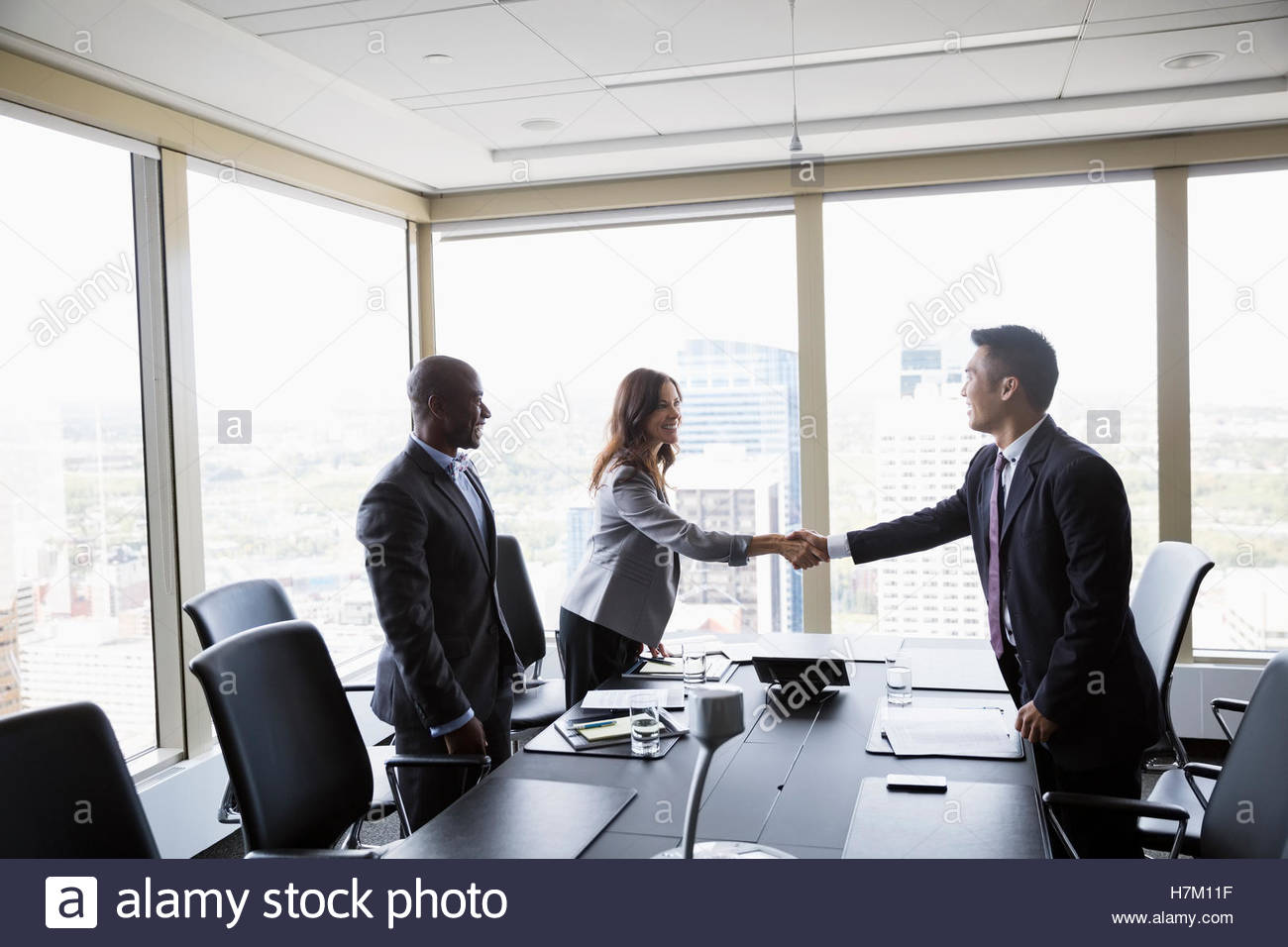 Business people handshaking in urban conference room meeting Stock Photo