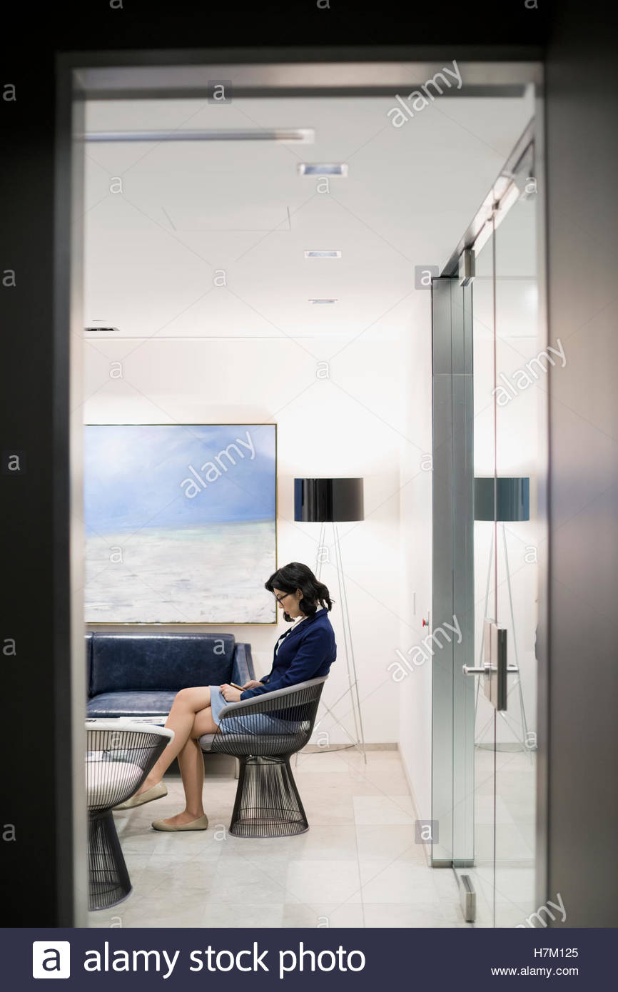Businesswoman using cell phone in office lobby - Stock Image