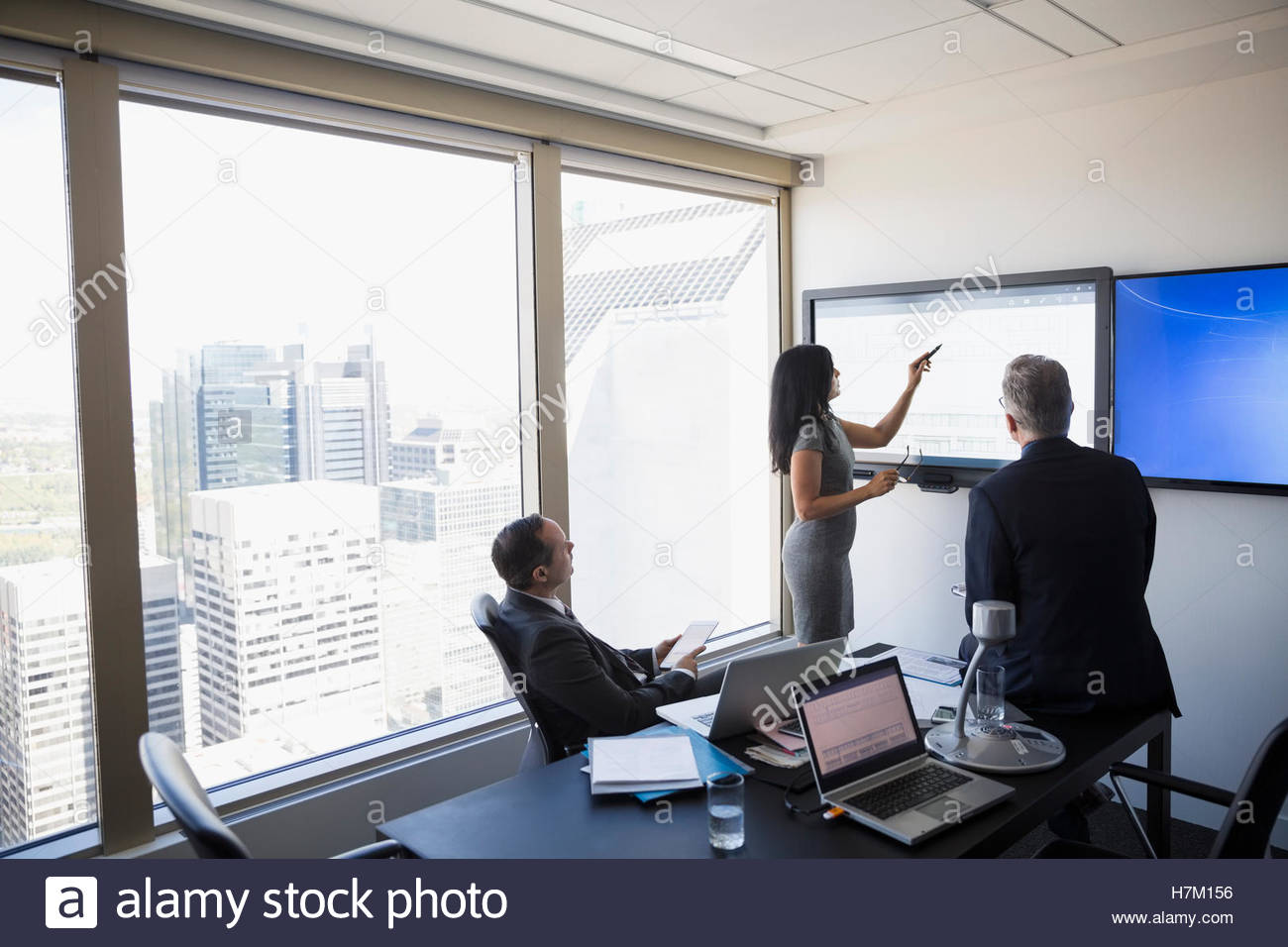 Business people meeting at large monitor in urban conference room - Stock Image
