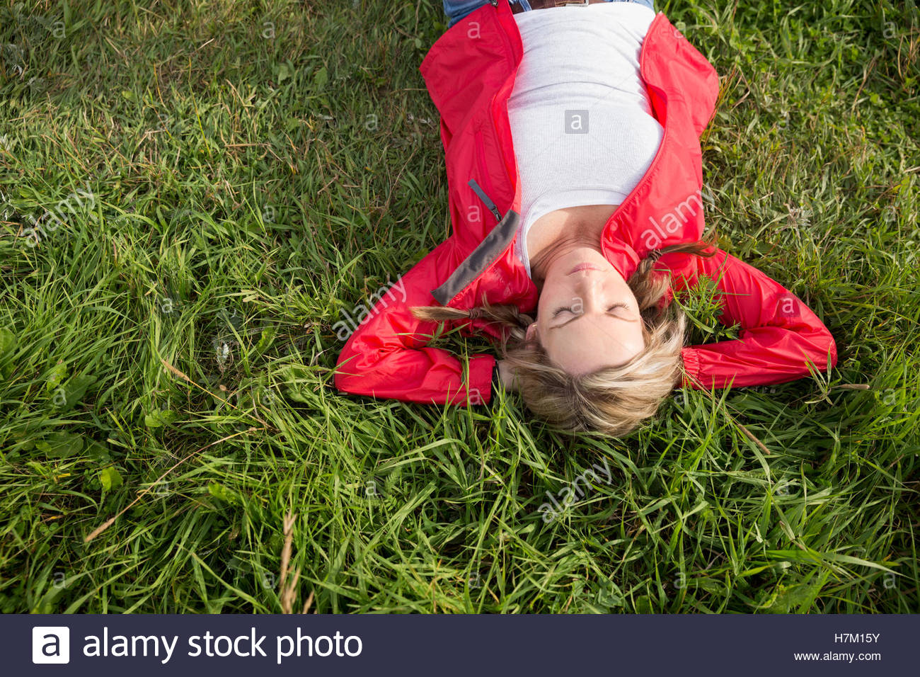 Serene woman laying relaxing with hands behind head in grass - Stock Image