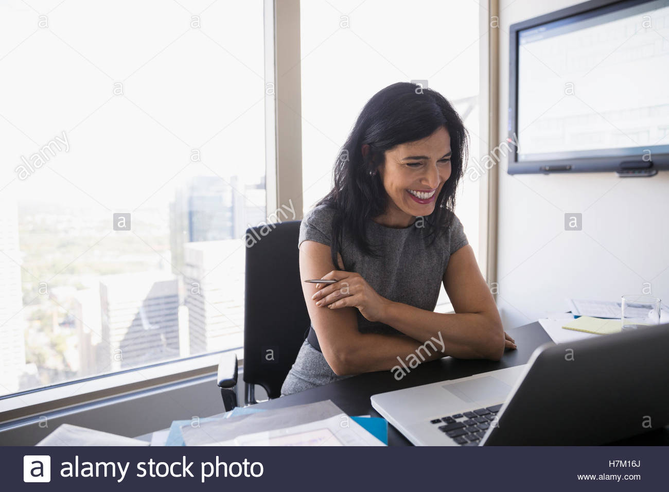 Smiling woman video conferencing at laptop in conference room - Stock Image