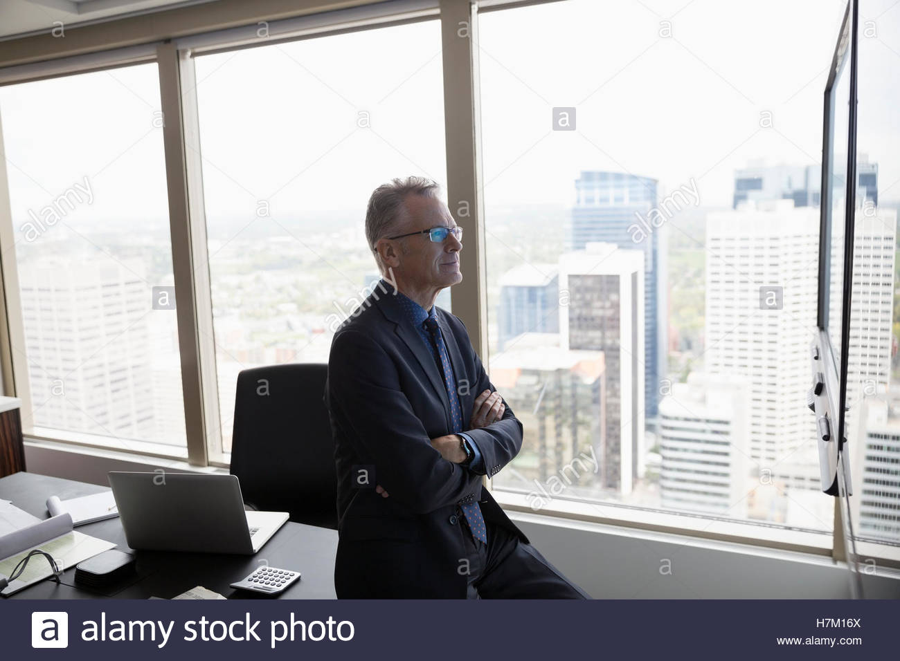 Serious businessman at television screen in urban conference room - Stock Image