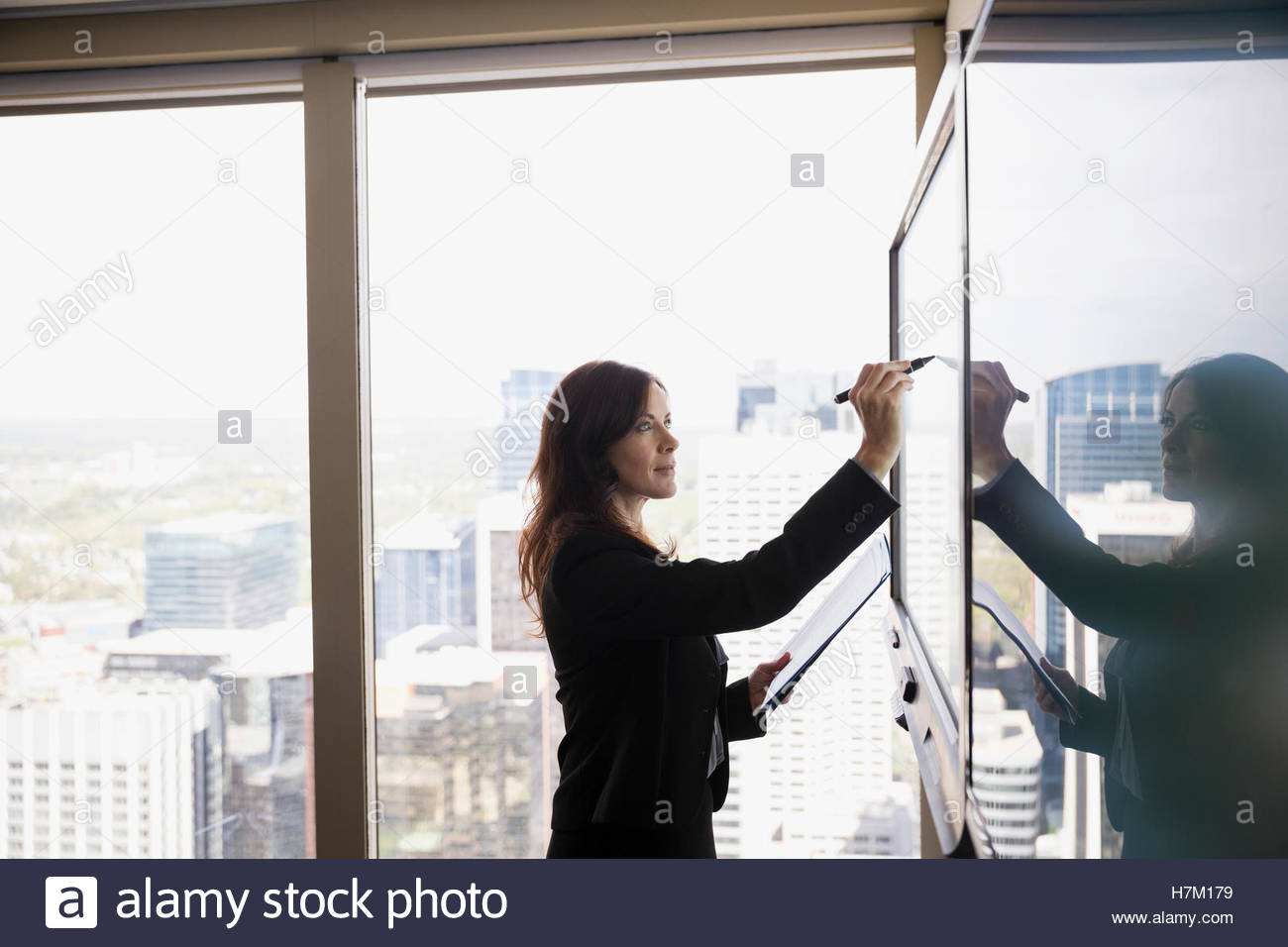 Businesswoman using stylus at large monitor in urban conference room - Stock Image