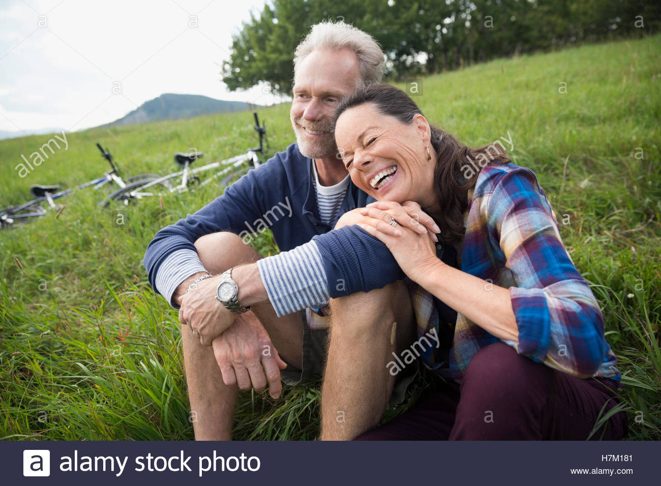 Laughing senior couple relaxing near mountain bikes in remote rural field - Stock Image