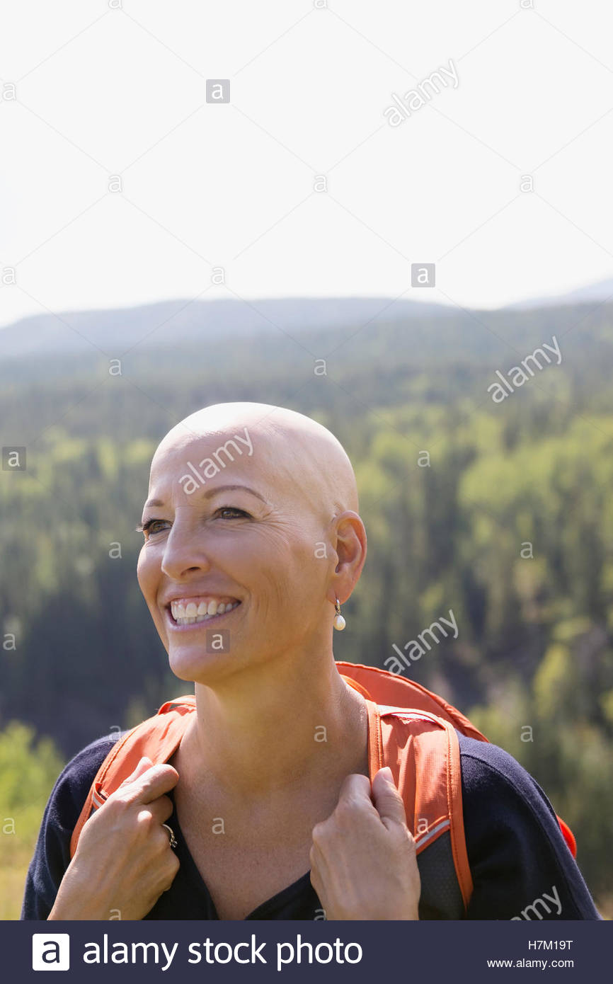 Smiling female cancer survivor with shaved head hiking with backpack in sunny woods - Stock Image
