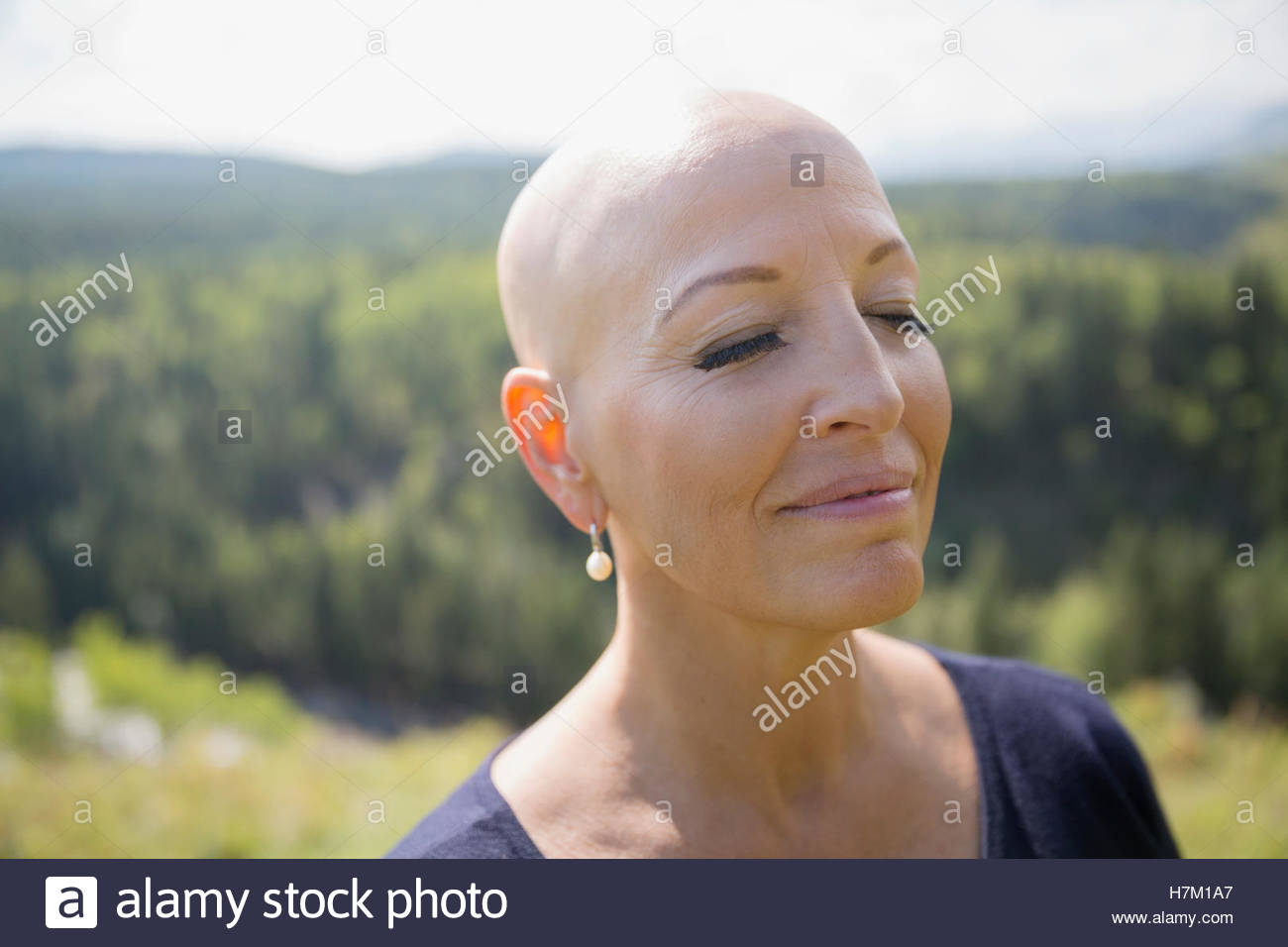 Close up serene female cancer survivor with shaved head and eyes closed - Stock Image
