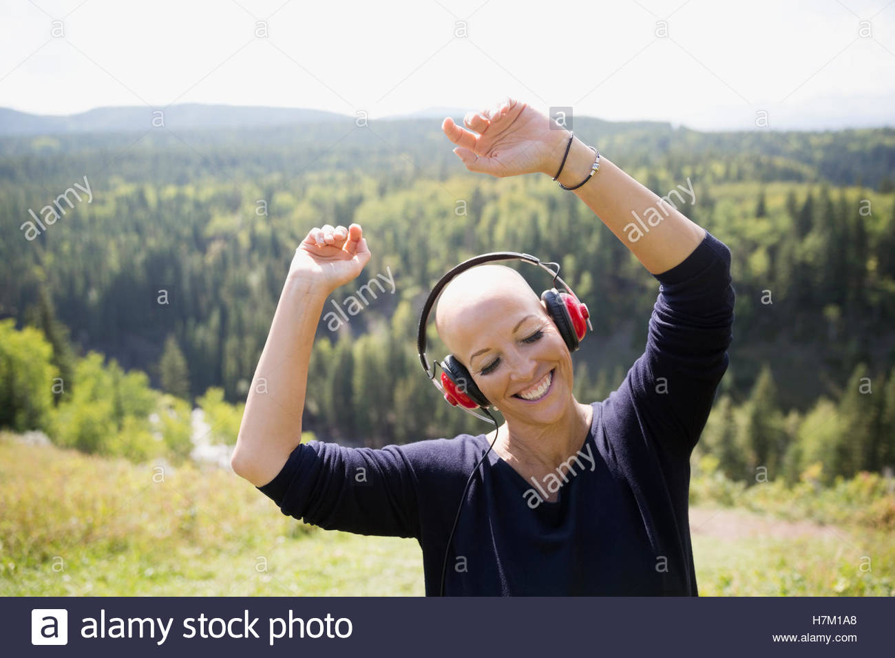 Female cancer survivor with shaved head dancing listening to music with headphones on sunny remote hilltop - Stock Image