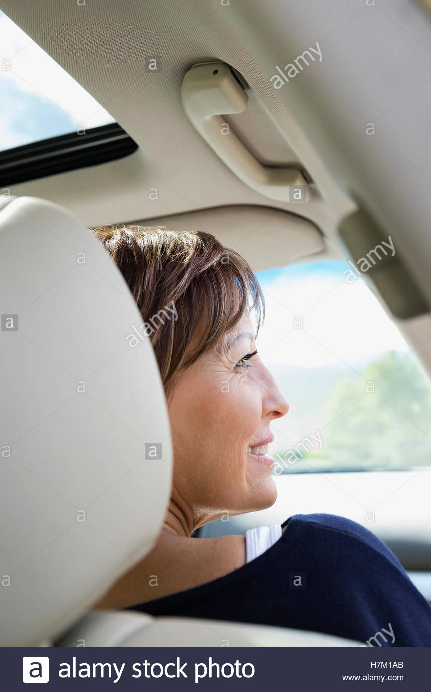 Smiling mature woman looking through window inside car - Stock Image