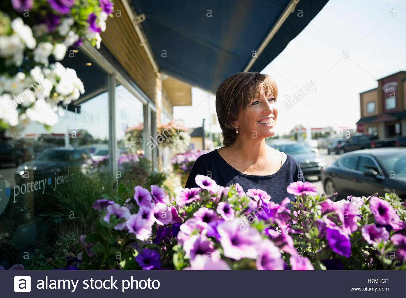 Smiling mature woman at sunny flower shop storefront - Stock Image