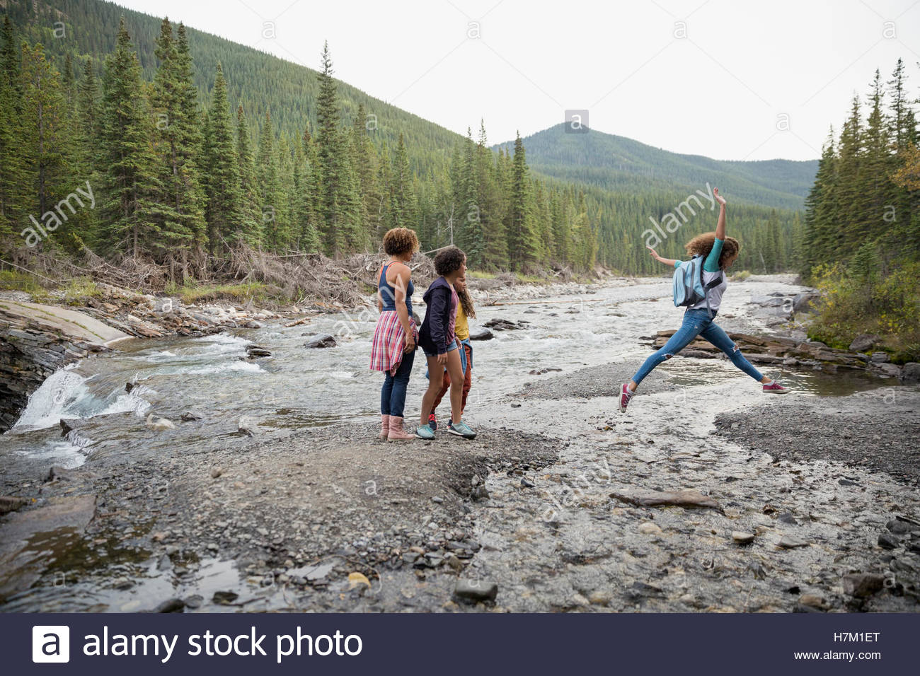 Mother and daughters hiking jumping across craggy creek - Stock Image