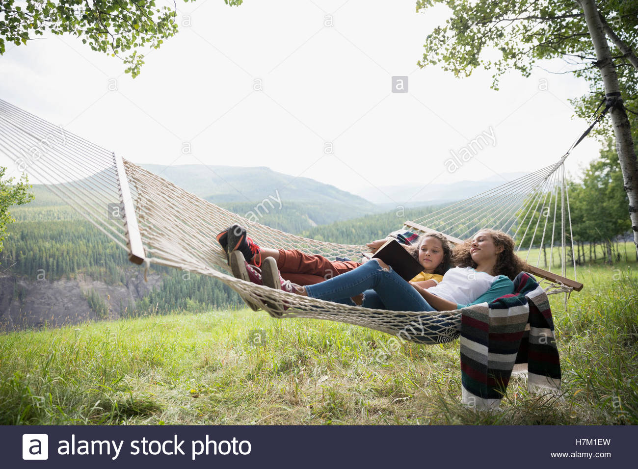 Sisters laying in rural hammock reading book - Stock Image