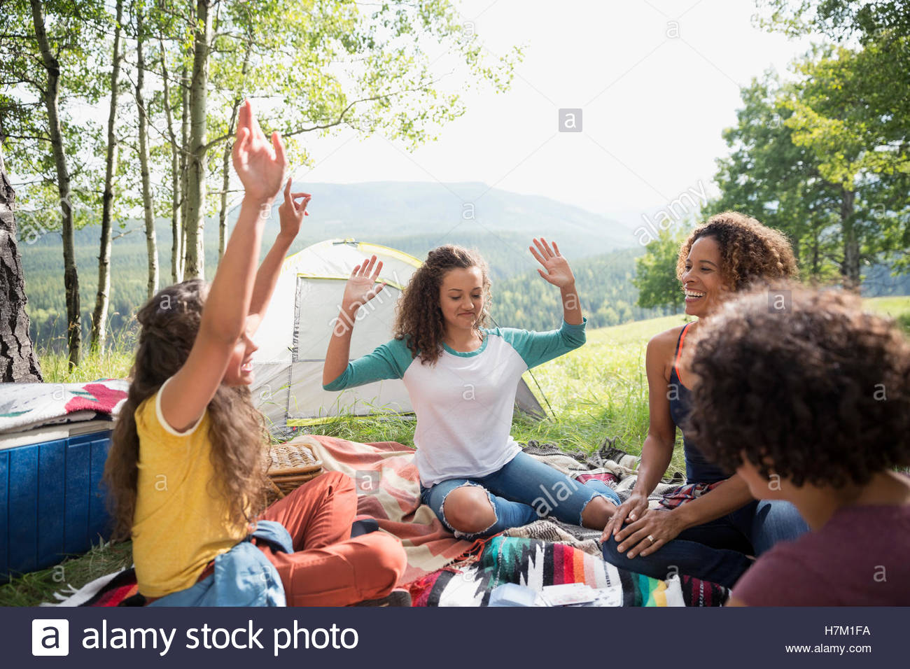 Mother and cheering daughters playing game at rural campsite - Stock Image