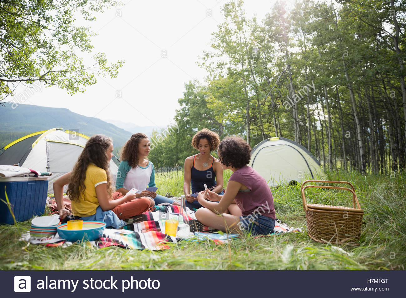 Mother and daughters playing card game on blanket at rural campsite - Stock Image