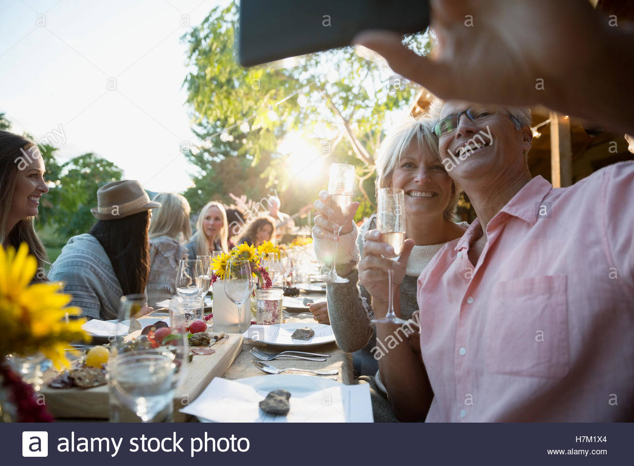 Couple drinking champagne and taking selfie at outdoor harvest dinner party Stock Photo