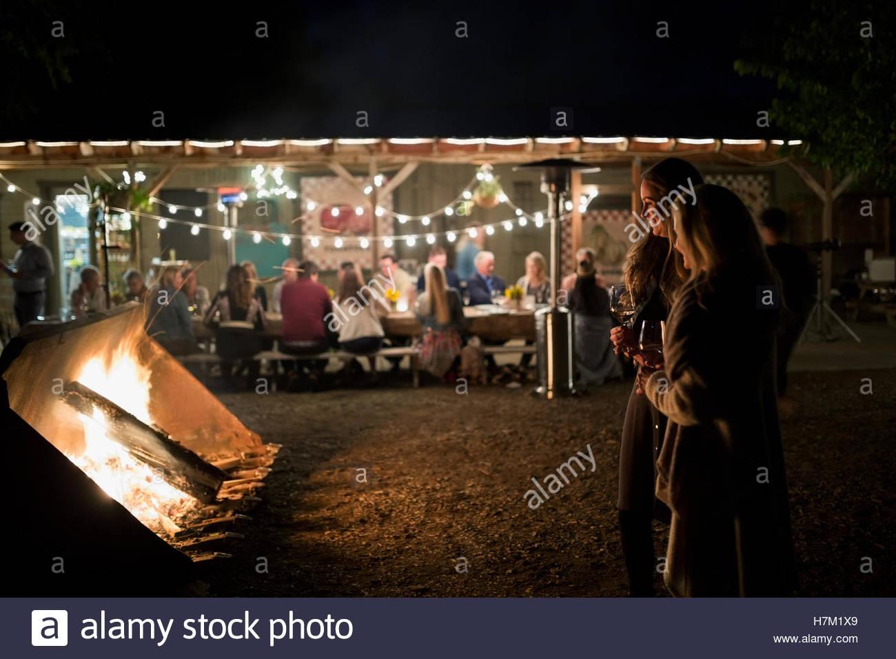 Friends enjoying bonfire and string lights illuminating outdoor dinner party - Stock Image