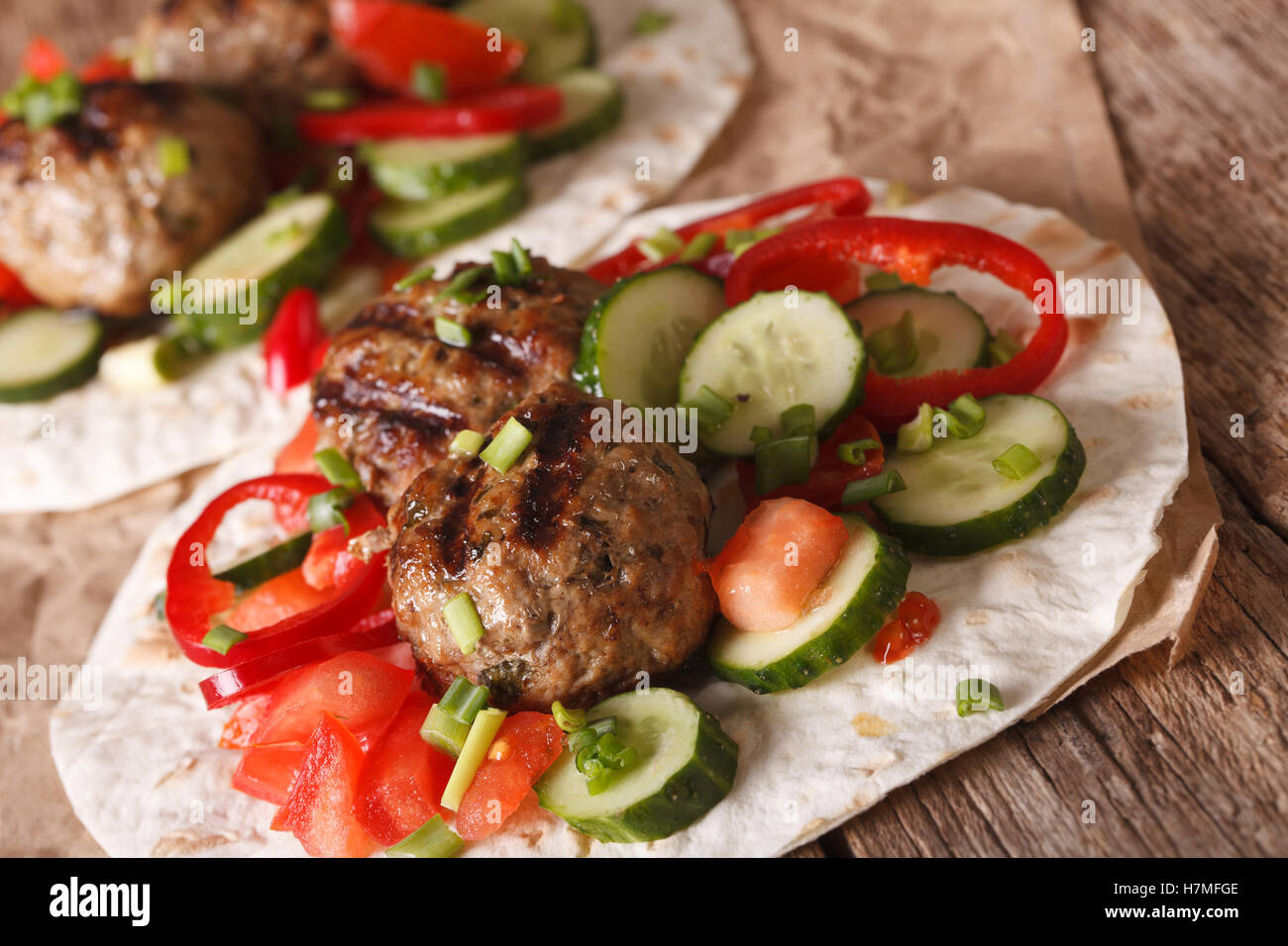 Arabian food: meat balls with fresh vegetables on a flat bread close up on the table. horizontal - Stock Image