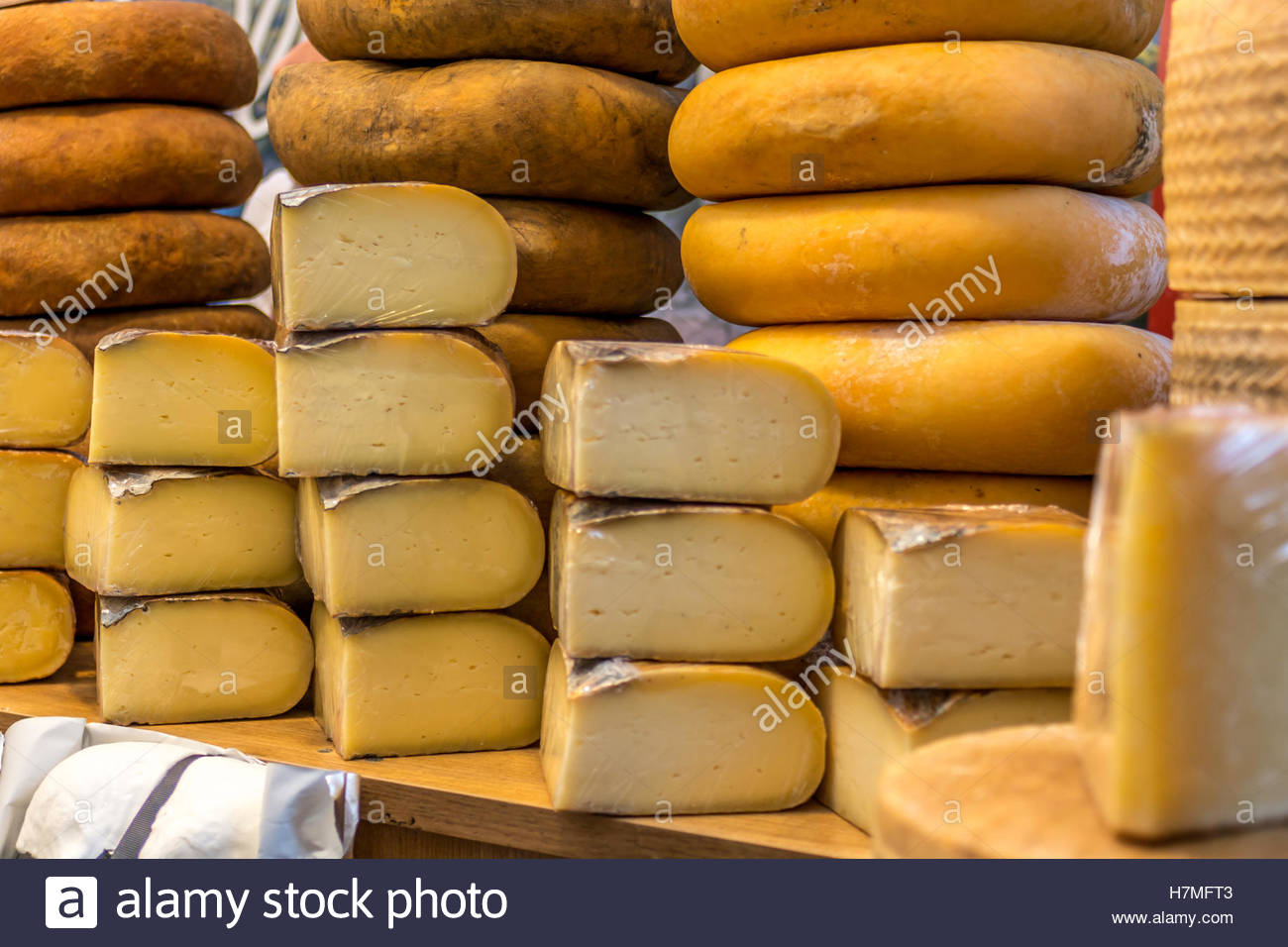 Artisan cheeses exposed in the artisan food market. - Stock Image