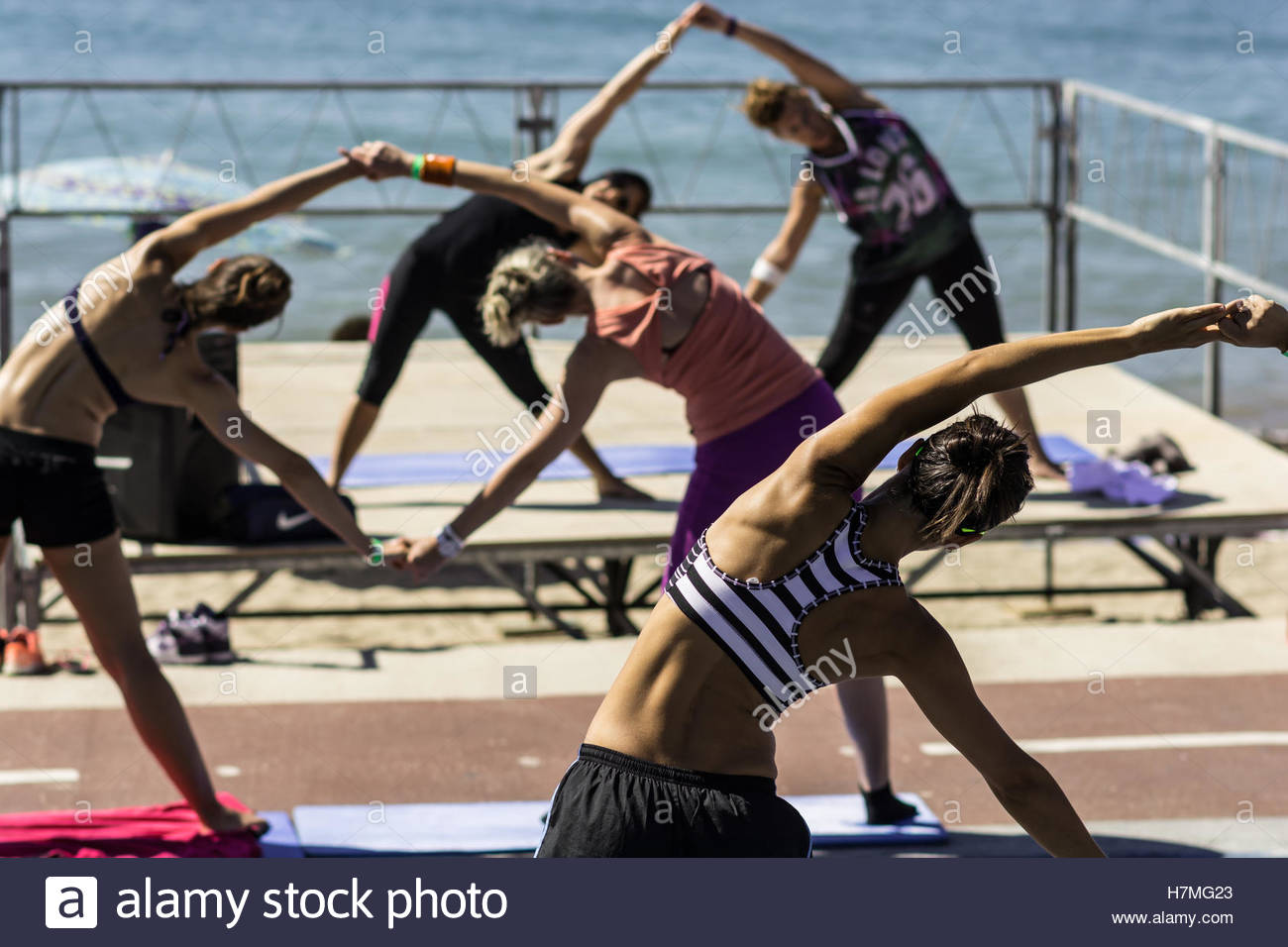 Women during a fitnees class outdoor on a sunny day in front of the sea. Doing side crunches - Stock Image