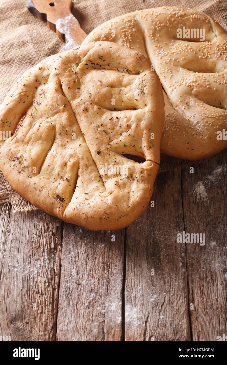 Fugasse French bread with sesame seeds and herbs closeup on the table. vertical, rustic - Stock Image