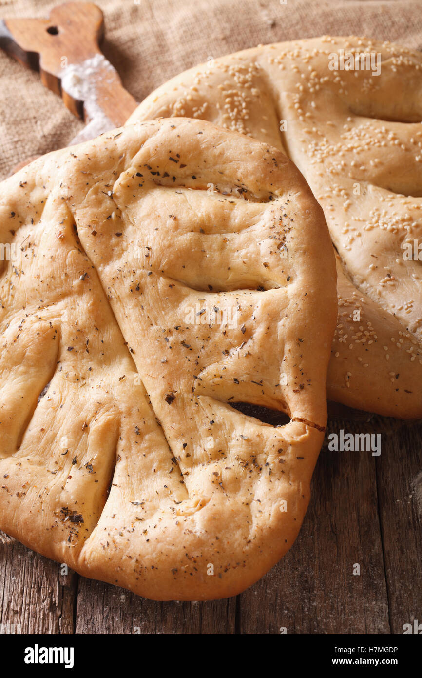 Traditional French bread Fugasse with sesame seeds and herbs macro on the table. vertical - Stock Image