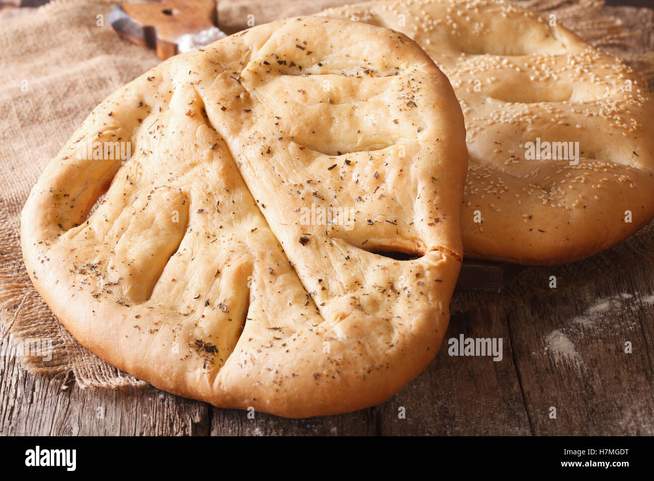 Homemade Fugasse French bread with sesame seeds and herbs closeup on the table. horizontal - Stock Image