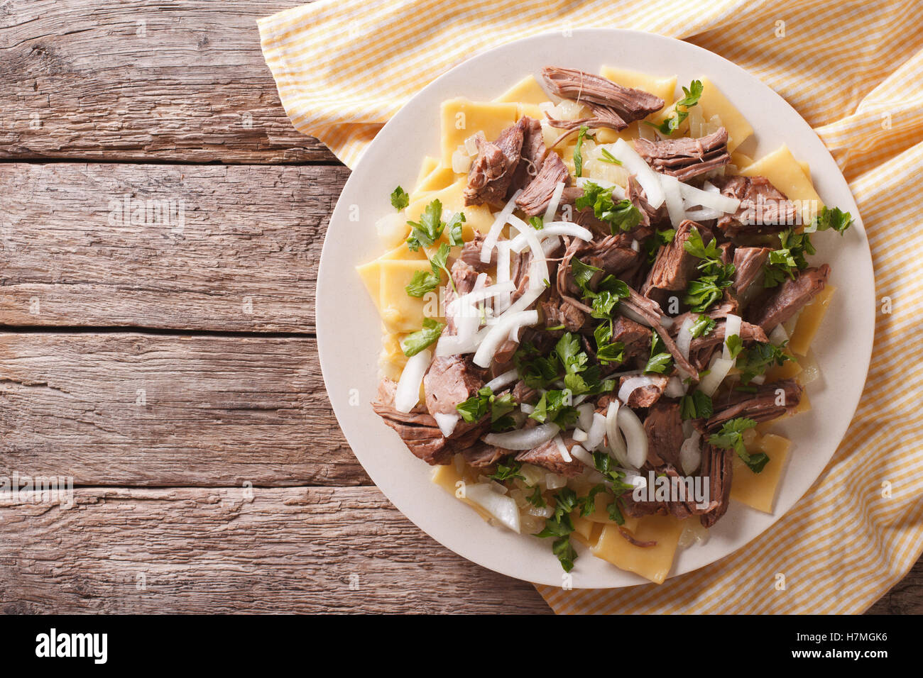 Beshbarmak dish: noodles with lamb and onion close-up on a plate on the table. horizontal top view - Stock Image