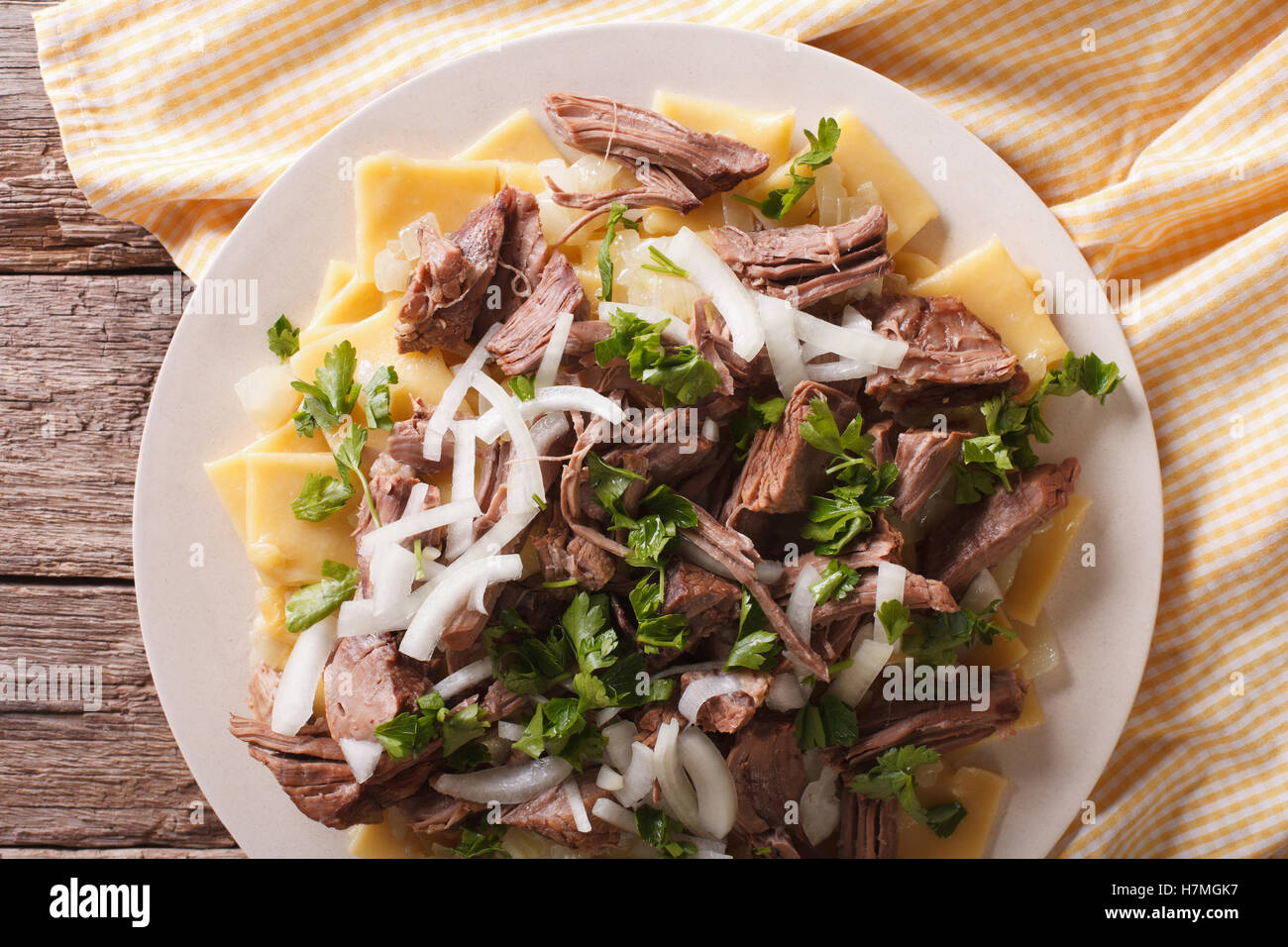 Asian beshbarmak - noodles with lamb and onion close-up on a plate on the table. horizontal top view - Stock Image