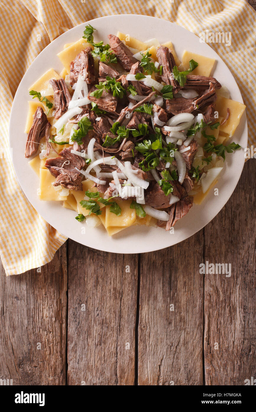Beshbarmak dish: noodles with lamb and onion close-up on a plate on the table. Vertical top view - Stock Image
