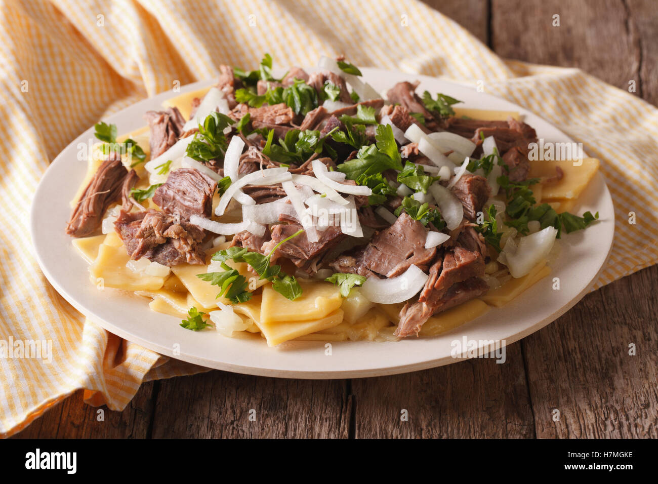 Beshbarmak dish: noodles with lamb and onion close-up on a plate on the table. horizontal - Stock Image