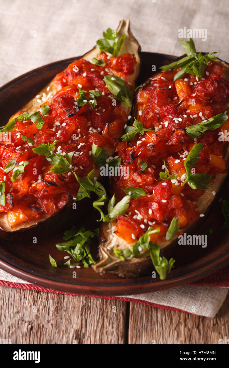 Turkish Cuisine: Half of eggplant stuffed with vegetables close-up on a plate. Vertical - Stock Image