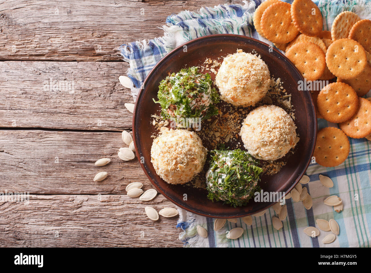 Goat Cheese balls with crackers herbs and pumpkin seeds on a plate. Horizontal view from above & Goat Cheese balls with crackers herbs and pumpkin seeds on a plate ...