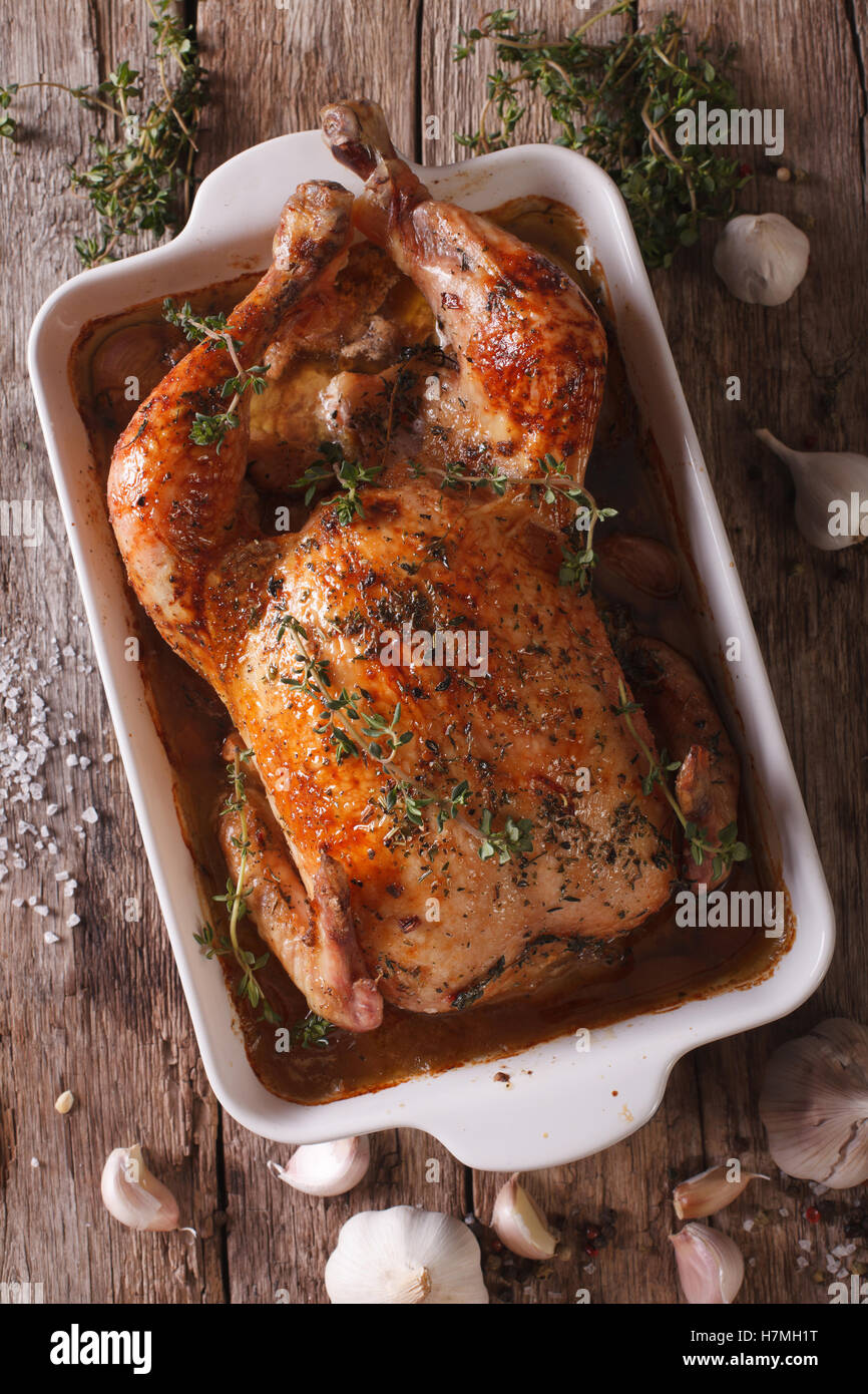 Baked Chicken with forty cloves of garlic and ingredients close-up on the table. vertical view from above - Stock Image
