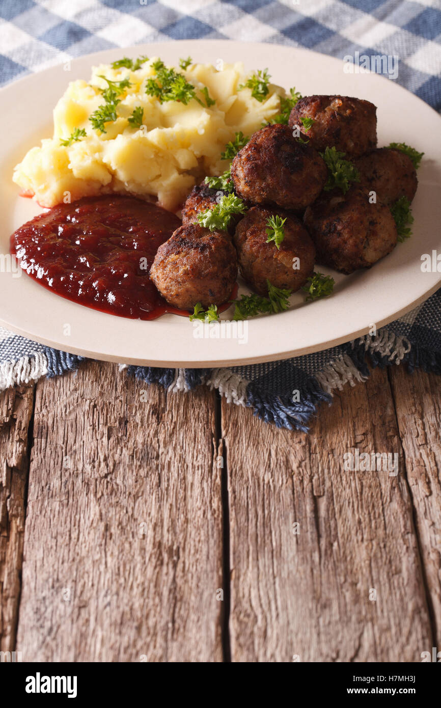 Swedish meatballs kottbullar, lingonberry sauce with a side dish mashed potato on the plate closeup. Vertical - Stock Image
