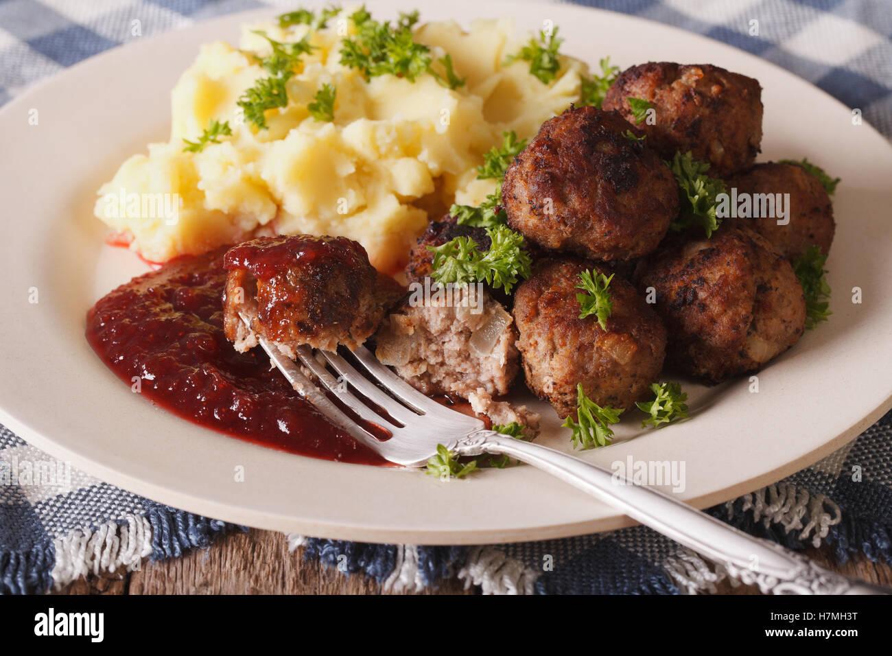 Swedish meatballs kottbullar, lingonberry sauce with a side dish mashed potato on the plate closeup. horizontal - Stock Image