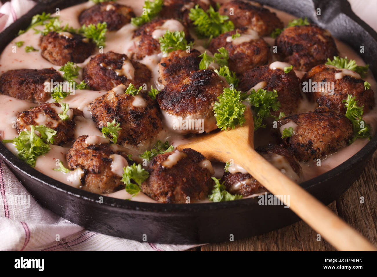 Swedish meatballs kottbullar in cowberry sauce in a pan macro. horizontal - Stock Image