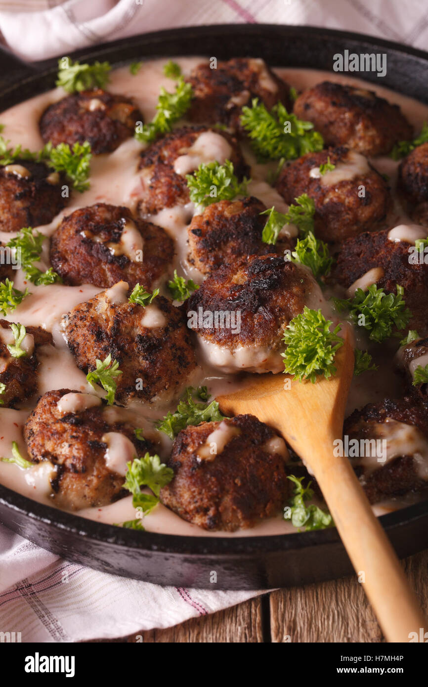 Swedish meatballs in a creamy cowberry sauce closeup on a frying pan. vertical - Stock Image