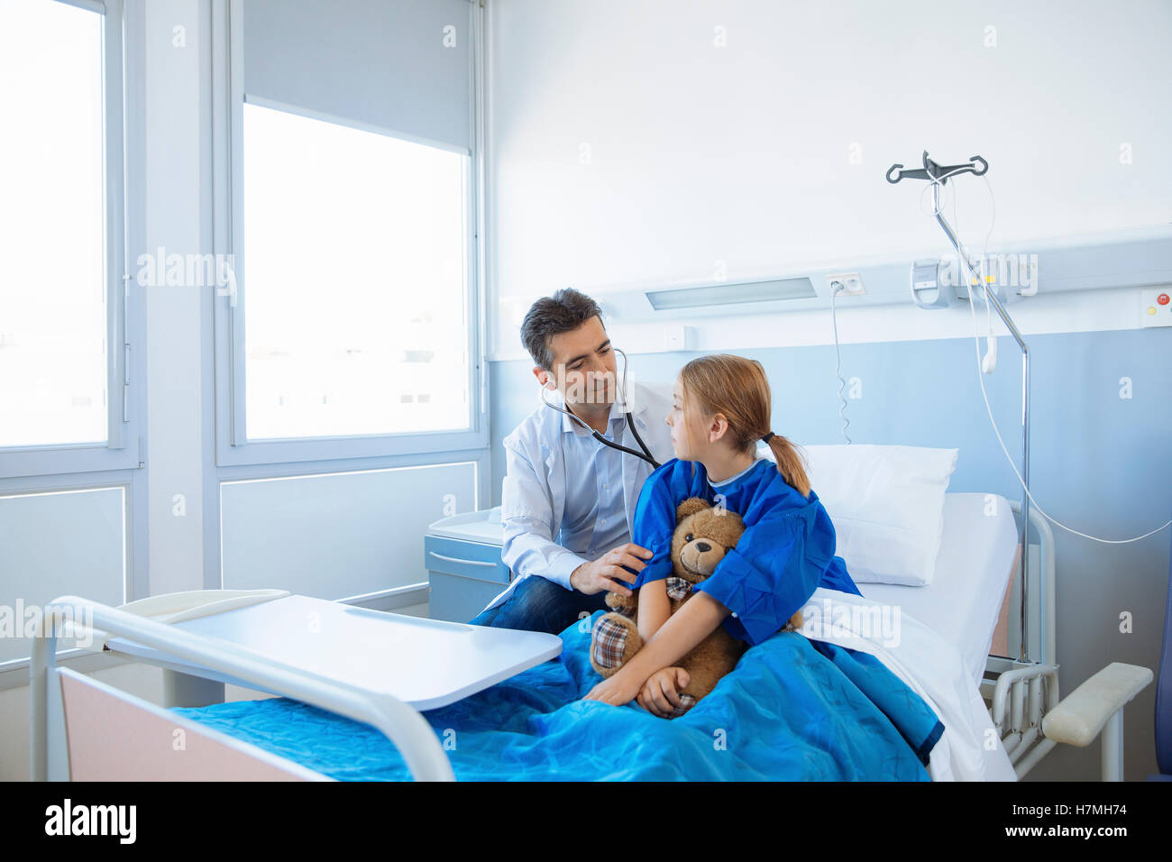 Doctor examining girl patient in hospital - Stock Image