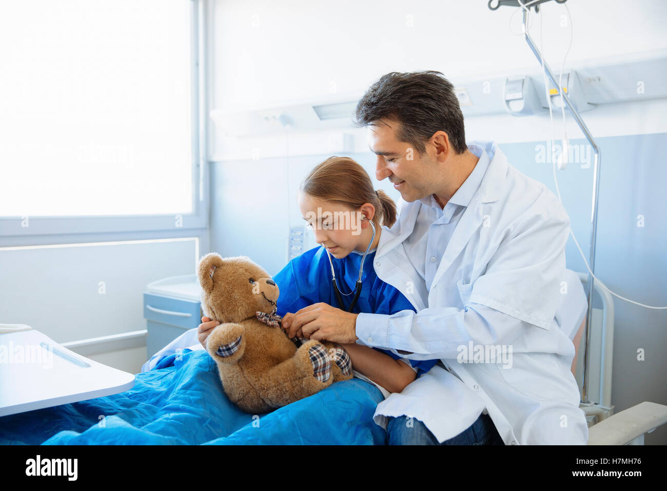 Doctor and girl patient examining a teddy bear - Stock Image