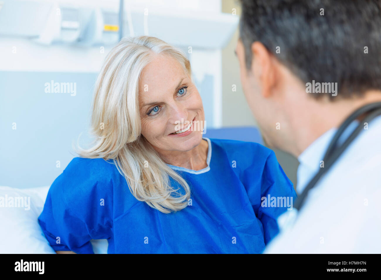Doctor examining senior patient in hospital - Stock Image