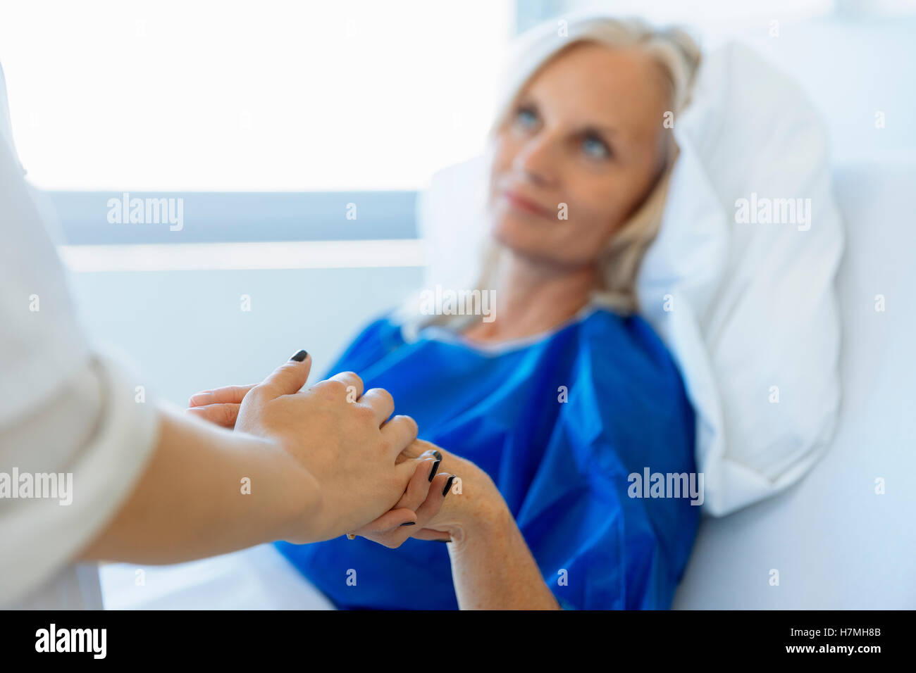 Doctor holding patient's hand in hospital room - Stock Image