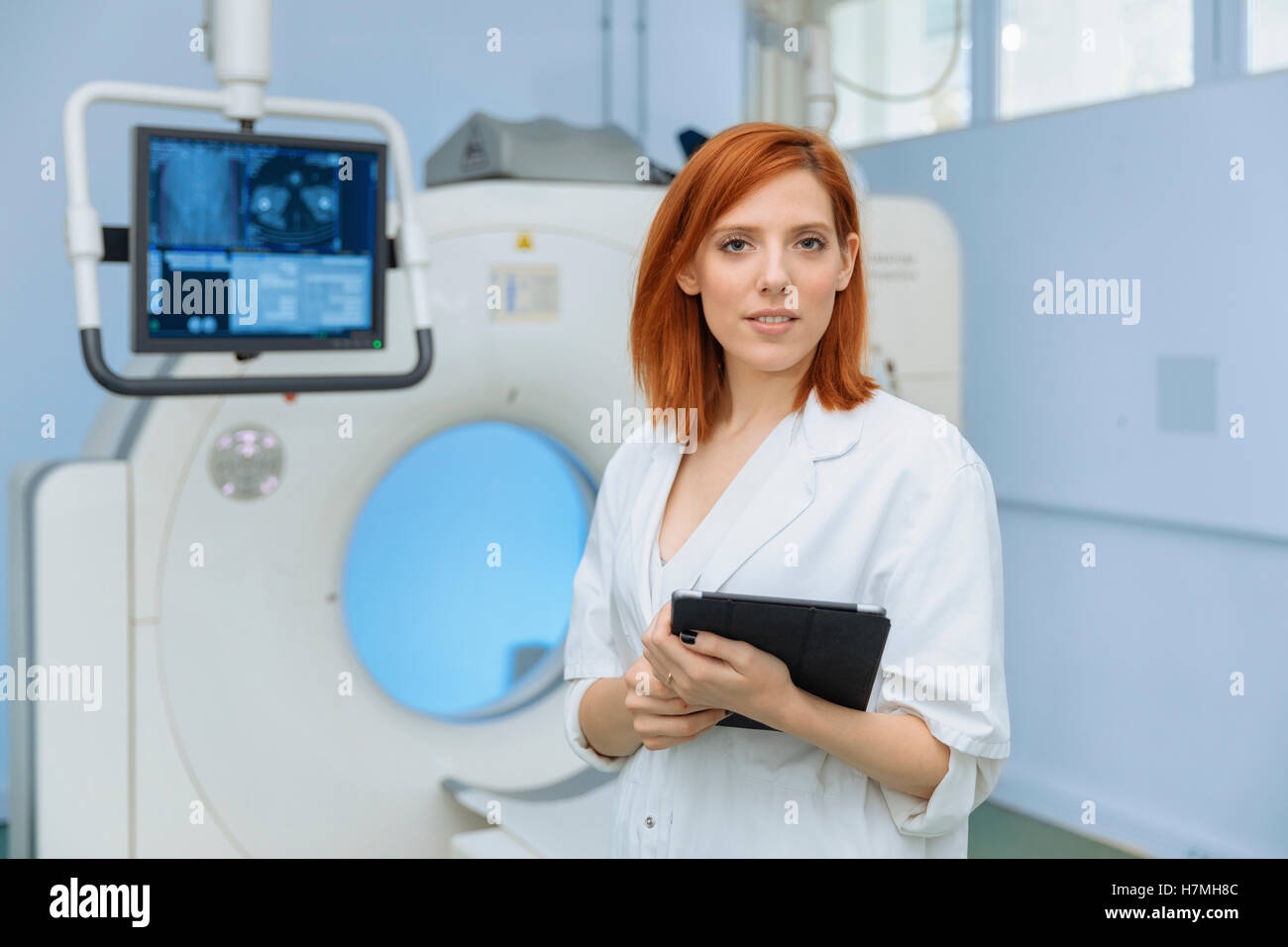 Portrait of a woman doctor in the scanner room - Stock Image