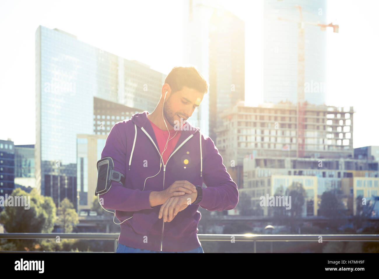 Fitness runner man checking heart rate with watch and trainer during outdoor trail running workout - Stock Image