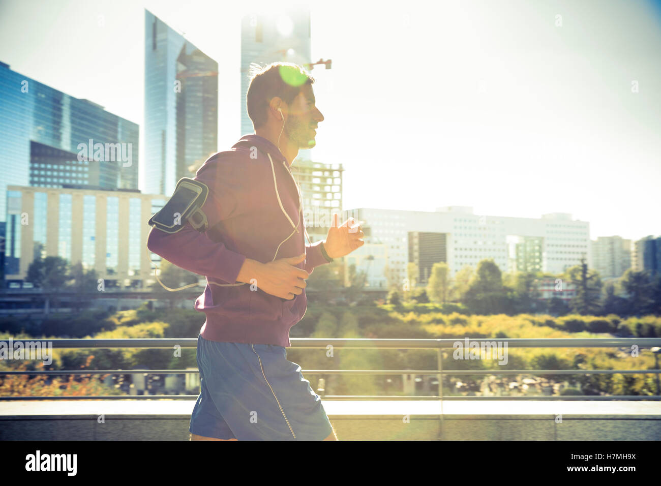 runner with earphones listening music running in the city - Stock Image