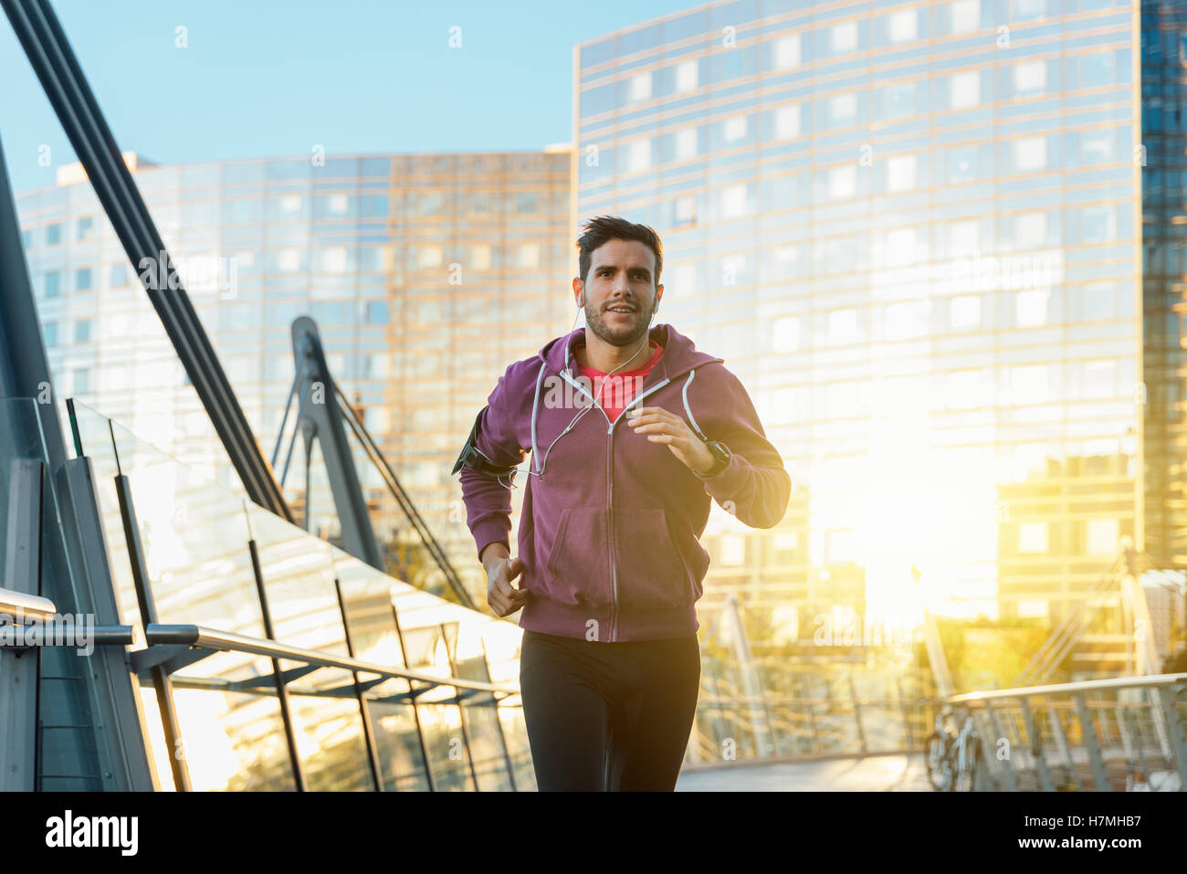 athlete with earphones running in the city - Stock Image