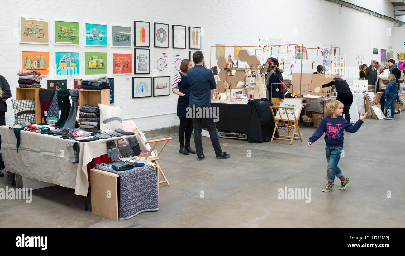 Young boy walking around designer stalls at the Renegade Craft Fair, an indoor indie designer market annual event Stock Photo