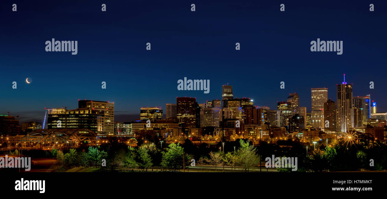 Skyline of Denver Colorado with moon at night - Stock Image