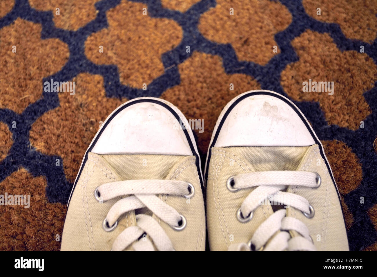 A pair of lightly soiled Converse All Star trainers on a doormat Stock Photo