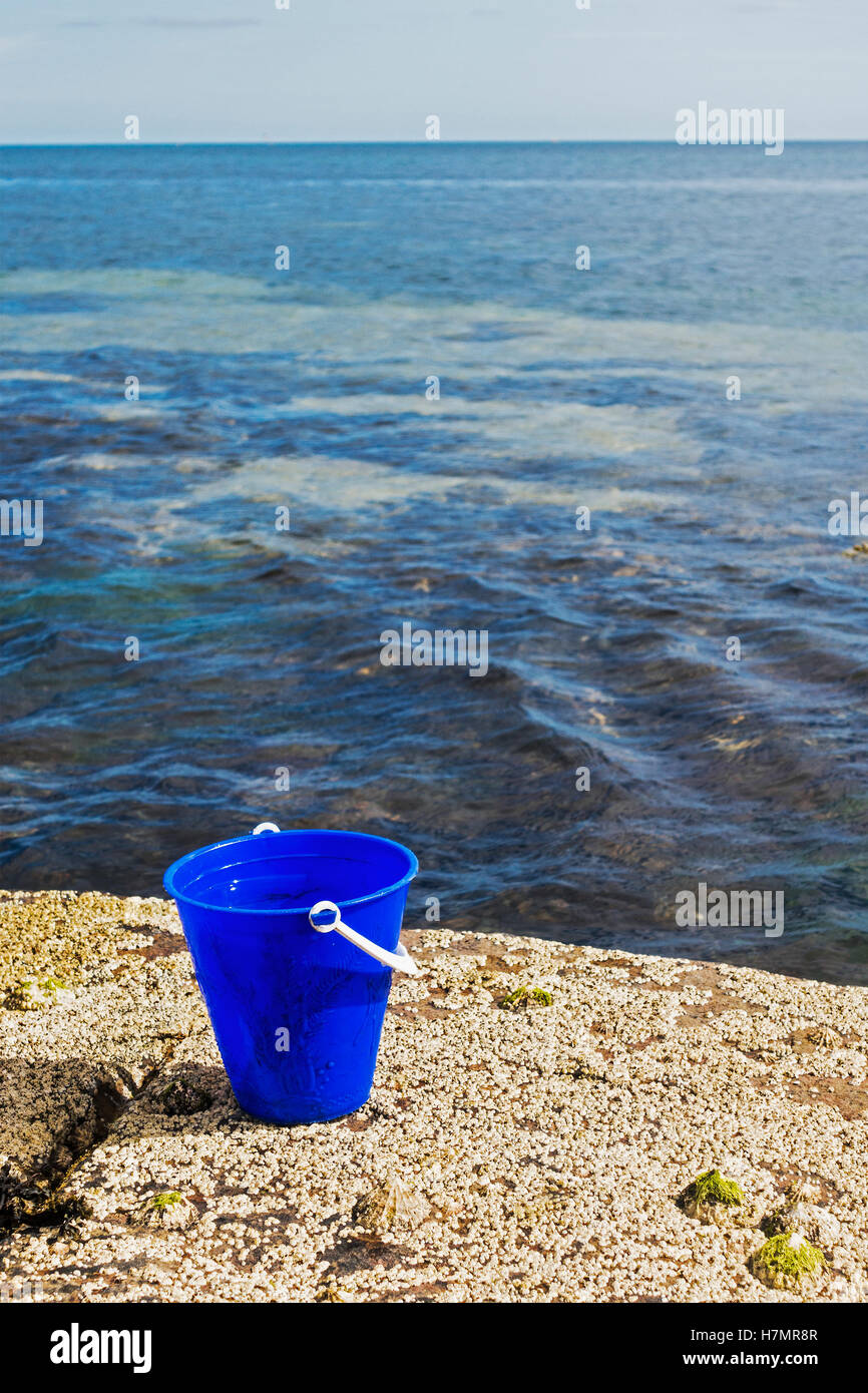 Bucket on rocks with defocussed sea and dead space. - Stock Image